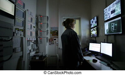 Female operator Looking At Multiple Camera Footage On Computers