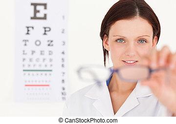 Female optician showing glasses - A female optician with eye...