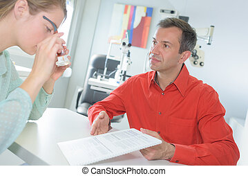 female optometrist having discussion with patient