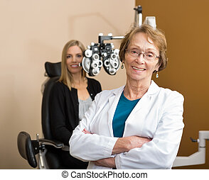 Female Optometrist With Patient In Background