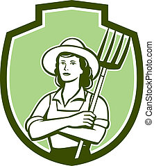 Illustration of a female organic farmer with pitchfork with hat facing front set inside shield crest on isolated bakcground done in retro style.