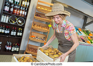 female owner holding various vegetables in crate at greenhouse