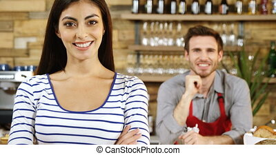 Female owner standing with arms crossed at counter 4k - ...