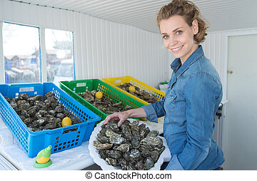 female oyster worker at oyster farm or restaurant