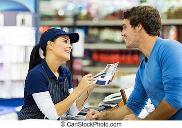 female paint store worker talking to customer
