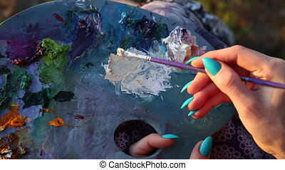 Female painter holding paintbrush over palette - Concept art...
