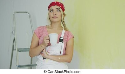 Female painter in overalls resting with drink - Beautiful...