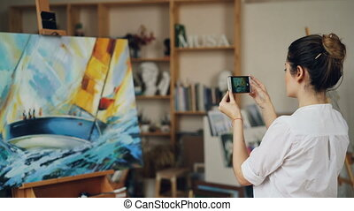 Female painter is taking photo of her beautiful picture...