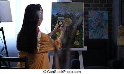 Female painter photographing artwork with peonies - Back...