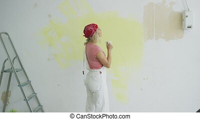 Female painter with drink looking at wall