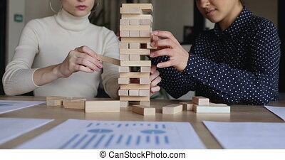 Female partners playing jenga game on office table, close up...
