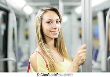 female passanger in train of metro - Casual smiling female...