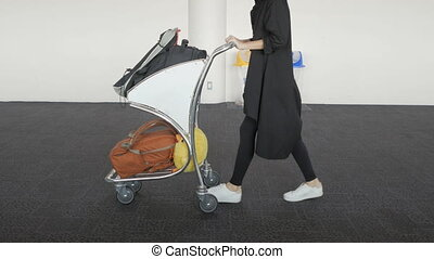 Female passenger legs, girl walk with trolley case at airport terminal