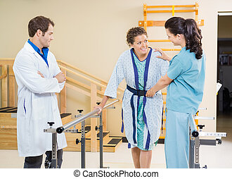 Female patient being assisted by physical therapists in hospital