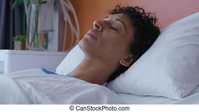 Female patient lying in a hospital bed