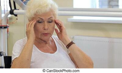 Female patient massages her head