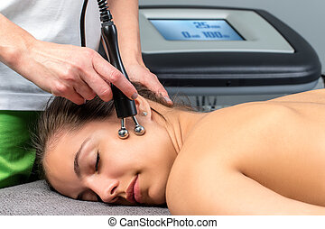 Female patient receiving electrotherapy  therapy on face.