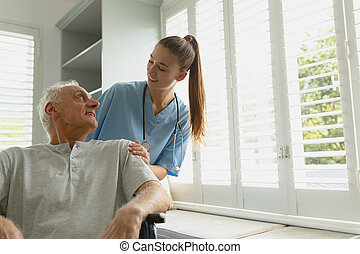 Female patient with active senior man in wheelchair at home