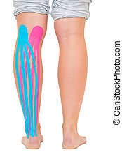 Female patients leg with applied pink and blue kinesio tape...