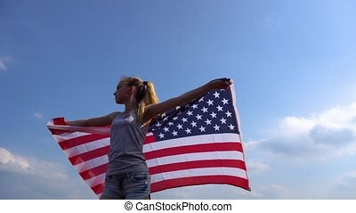 Female patriot holding USA flag in nature - Young teen...