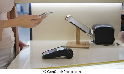 Female paying through new smart phone using NFC technology...