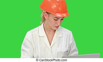 Female pensive architect using laptop and paper plan to check progress on a Green Screen, Chroma Key.