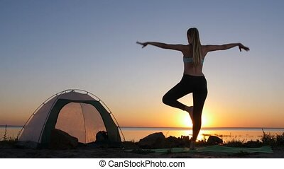 Female performing tree yoga pose while camping