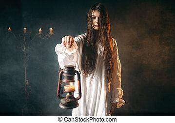 Female person holds kerosene lamp, dark magic