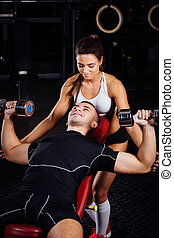 Female personal fitness instructor helping a young man at gym.