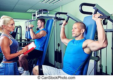 Female personal fitness trainer with two Athlete man in gym