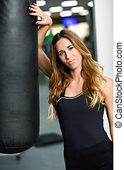 Female personal trainer with punching bag in a gym