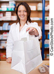 Female Pharmacist Giving Medicine To Customer - Young female...
