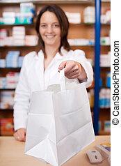 Female Pharmacist Giving Medicine To Customer