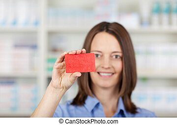 Female Pharmacist Holding Business card In Pharmacy - ...
