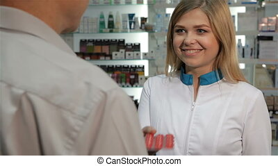 Female pharmacist offers lozenges to the client at the drugstore