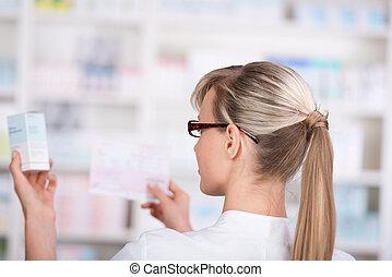 Female pharmacist picks up medicine form the shelf