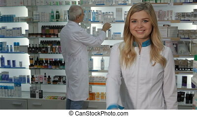 Female pharmacist shows her thumb up at the drugstore
