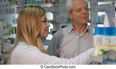 Female pharmacist shows medicine to the male customer