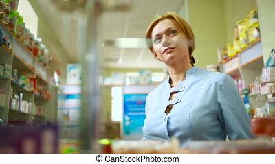 female pharmacist standing at counter in pharmacy