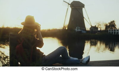 Female photographer sits on a sunset lake pier. Girl with...