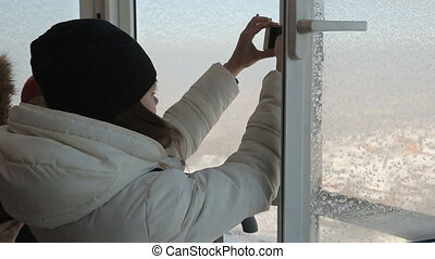 Female-photographer takes pictures with smartphone through open window of a high building in winter