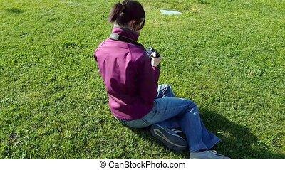 Female photographer sitting on grass using DSLR camera