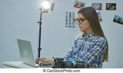 Female photographer working in her professional photo studio with a laptop, camera and lighting equipment