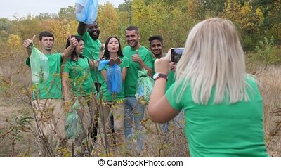 Female photographing volunteers in forest
