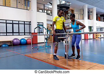 Female physiotherapist assisting disabled man walk with parallel bars in sports center
