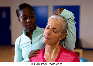 Female physiotherapist giving neck massage to active senior woman in sports center
