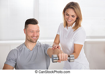 Female Physiotherapist Helping Man To Exercise