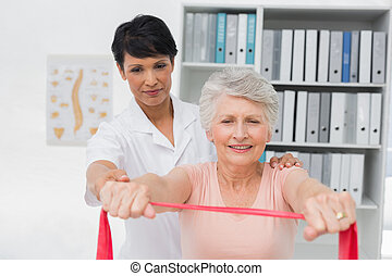 Female physiotherapist massaging senior womans back in the...