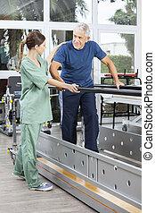Female Physiotherapist Motivating Senior Man To Walk Between...