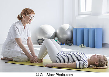 Female physiotherapist working with child in bright occupational room